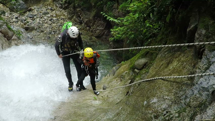 BANOS DE AGUA SANTA, ECUADOR - 7 JANUARY 2015: Young boy with instructor rappelling Cashaurco waterfall in Ecuadorian Andes in Banos de Agua Santa on JANUARY 7, 2015