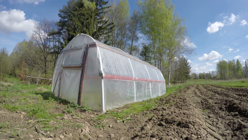 plastic greenhouse in spring wind and clouds motion in farm. Timelapse 4K