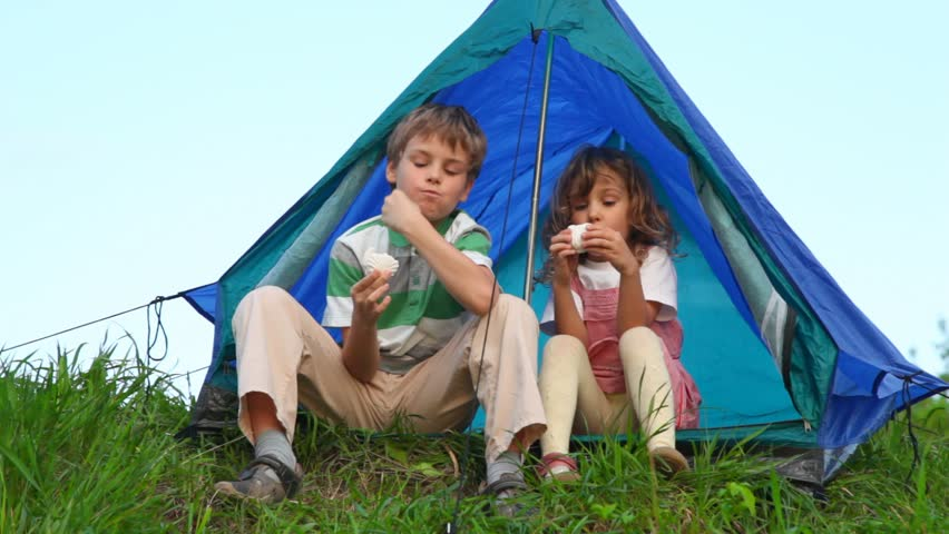 boy with girl sitting in tent and eating cakes - HD stock video clip