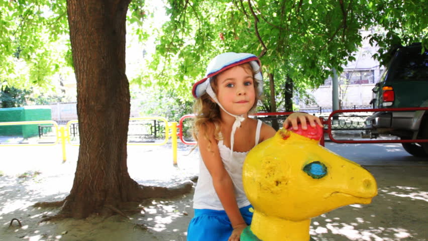 girl sits on toy horsey in middle of children's playground  - HD stock video clip
