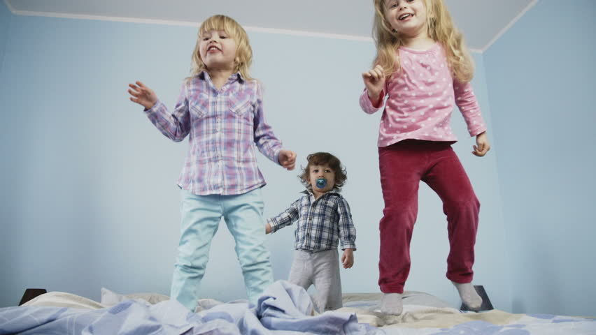 Little kids jumping on bed. Shoot on Digital Cinema Camera in slow motion - ProRes 422 codec.